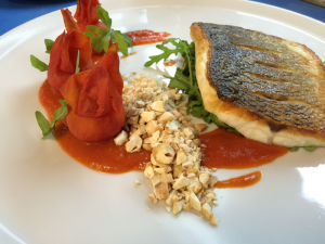 SEA BASS SAUTEED FILLET WITH SAUCE OF TOMATOES AND ORANGES, ARUGULA, ROASTED CASHEWS AND BOTTARGA